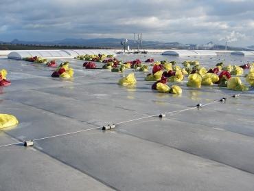 Provizorní přitížení havarované části střechy pytli s pískem