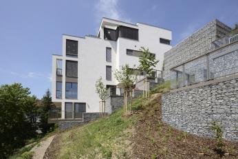 Na terén navazují domy terasami a zídkami zgabionů