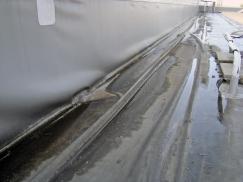 Obr. 4: Havarovaný detail střechy v důsledku vytržení lišty u paty atiky znamená deformaci fólie, znesnadnění odtoku vody