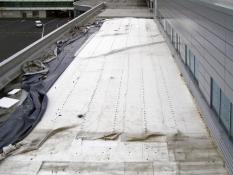 Obr. 6: Havárie plochých střech v důsledku námahy větrem – selhání kotvení okraje střechy bylo první fází selhání celé střechy