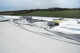 Obr. 7: Havárie plochých střech v důsledku námahy větrem – selhání kotvení okraje střechy bylo první fází selhání celé střechy