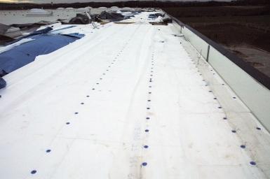 Obr. 21: Důsledky nesprávné geometrie kotev v přesahu střešní fólie – větrem utržená hydroizolace střechy