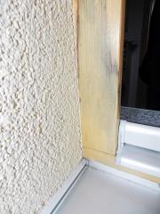 Obr. 4: Chybně zabudovaný okenní rám (dokončená fasáda po osmi měsících), zdegradovaná montážní pěna – zůstala porézní, což je následek chybné aplikace bez zvlhčení ostění. Dochází ke kondenzaci v připojovací spáře, následně ke zvýšení vlhkosti nad 18 % a separaci lazury a vzniku plísně pod lazurou.