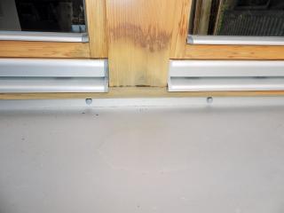 Obr. 5: Chybně osazený vnější hliníkový parapet – malý sklon parapetu (pod 6 °, viz voda stojící na parapetu); hniloba v konstrukčním spoji sloupku; parapet není tepelně separován od dolního vlysu okenního rámu. což vede k tvorbě rosného bodu a zvyšování vlhkosti a následně k separaci lazury a tvorbě plísní.
