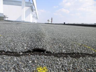 Obr. 21: Deformace asfaltového pásu nad stykem neukotvených desek polystyrenu má za následek delaminaci spojů a zatékání