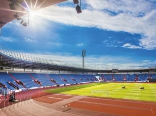 Nové kryté tribuny uzavírají sportovní ovál po stranách původní tribuny