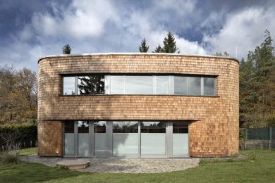 Pro fasádu měli autoři projektu více variant řešení, nakonec se rozhodli pro šindele, které dobře kopírují měkký tvar stavby