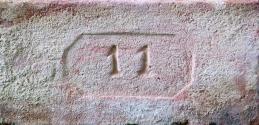 Plná cihla s kolkem 11 v osmibokém rámečku, běžný formát (290×140×65 mm), 1. polovina 20. století. U takto značených cihel je problematická přesná identifikace původu.