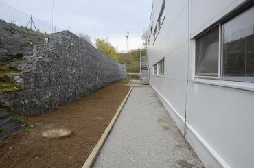 Obr. 4: Opěrná gabionová stěna, za zdí vlevo frekventovaná silnice, vpravo výrobní hala, před zdí zelený pás