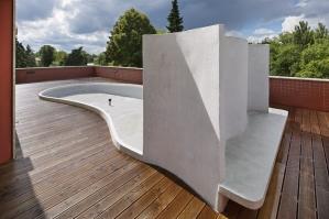 Střešní terasa s organicky tvarovaným záhonem, větrolamem a lavičkou
