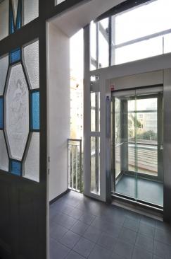 Mezipodesty snovým výtahem: design výtahové šachty i kabiny je prosklený a odlehčený, aby co nejméně omezil prosvětlení stěn se secesními motivy