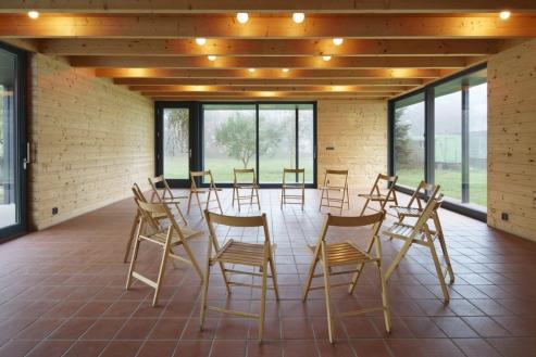 V komunitní místnosti je důležitý motiv kruhu při uspořádání židlí nebo jako osvětlení na stropě. Prosklená fasáda se otevírá velkoplošnými posuvnými stěnami.