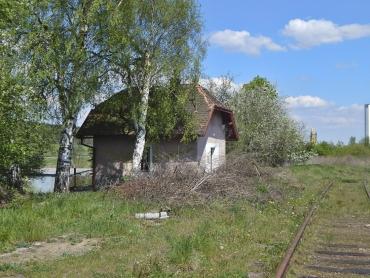Bývalý strážní domek se nachází severovýchodně odnástupiště. Fasádou ipolovalbovým zastřešením reaguje navýpravní budovu.