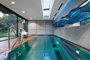 Vnitřní bazén s atmosférou venkovního koupání: posuvné systémy Schüco propojují bazén s terasou. Vše je pro maximální pohodlí ovládáno automaticky díky systému Schüco e-slide s elektrickým pohonem.