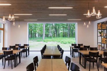 Velkoformátové zasklení vrestauraci otevírá prostor do přírody. Lehký dřevěný podhled ukrývá instalační trasy kanalizace, topení, elektro a dalších médií.
