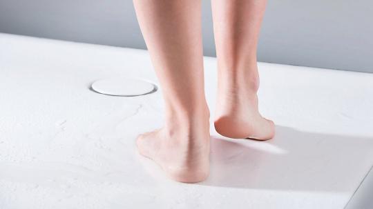 Pohodlné sprchování. Odpad ploché vaničky Geberit Setaplano je umístěný nenápadně na straně, aby se chodidla během sprchování nemusela vyhýbat odtokové krytce, ani odtékající vodě.