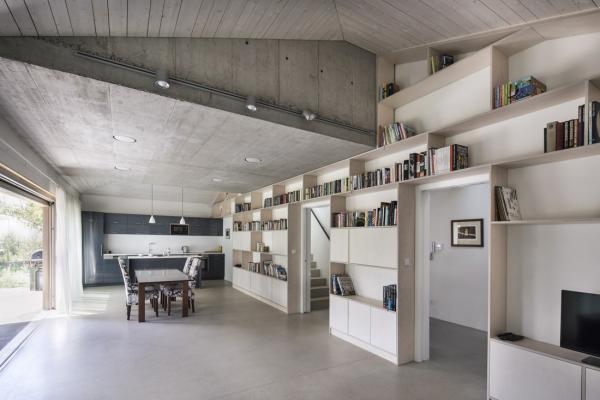 Klidné a přirozené plochy betonu v kombinaci se světle mořeným dřevem odpovídají představám majitelů domu o současném, prosvětleném a prostorově velkorysém interiéru