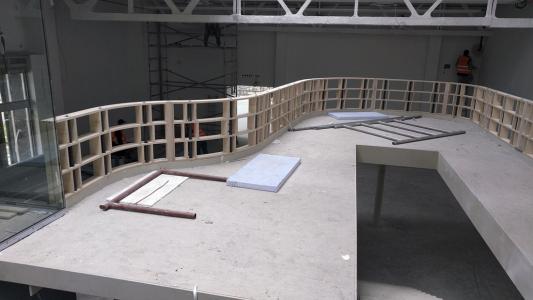 Jako dominantní interiérový prvek bylo do úrovně 2. NP navrženo vykonzolované balkonové těleso ve tvaru těla klavírního křídla