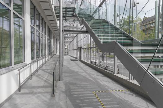 Předsazená celoskleněná konstrukce obvodové stěny vytváří meziprostor pro požární úniková schodiště, navíc má příznivý vliv na vnitřní mikroklima budovy a chrání ji před dopravním hlukem