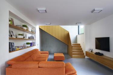 Na podlahách je litá polyuretanová stěrka, u schodiště propojujícího obě části stavby autor použil šedou broušenou fasádu, která je i vexteriéru masivní stavby