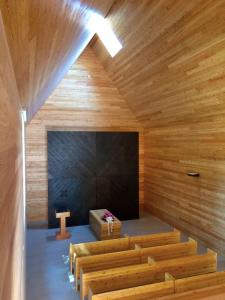 Interiér síně je obložený modřínovým dřevem, otevřený do krovu. Prosvětlují ho dvě velká okna.