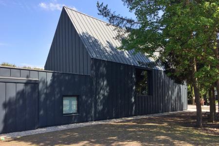 Provozní část má plochou střechu, fasádou navazuje na hlavní objekt