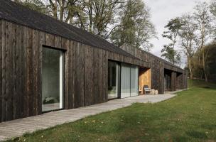 Dlouhou horizontální hmotu stavby spojuje tmavě opálené dřevo na fasádě i na střeše