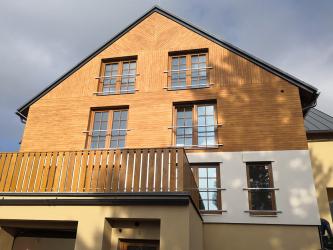 Omítka imitující dřevo na fasádě horských apartmánů