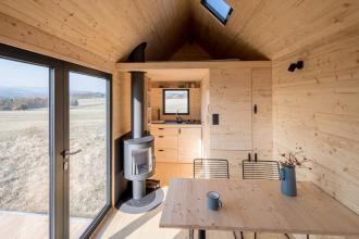 Pomocí polohování vestavěného nábytku se může přizpůsobit dispozice různým funkcím, na vyvýšeném lůžku v přízemí s dvěma řadami výsuvných šuplíků se po rozložení vyspí dva lidé (horní řada zásuvek jsou úložné prostory) a nahoře v patře nad plně vybavenou kuchyňkou je ještě manželská postel