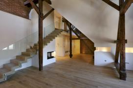 Schodiště vmezonetovém bytě má konstrukci socelovými schodnicemi, stupni zmasivního dřeva askleněným zábradlím