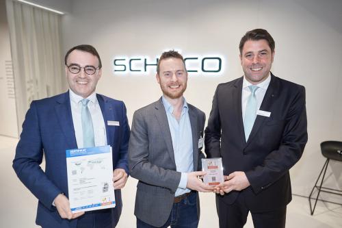 Edward Lowes (uprostřed) z Institutu pasivních domů (Passivhaus Institut) předává certifikát Markusi Herbstovi (vpravo), mluvčímu výkonného vedení společnosti Schüco Polymer Technologies KG, a Christianu Fischerovi (vlevo), vedoucímu technologického oddělení společnosti Schüco Polymer Technologies KG