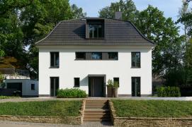 Pohled z ulice: Symetrické uspořádání oken a dveří strukturuje fasádu i střechu. Opakuje se zde motiv úzkých, vertikálně orientovaných dvoukřídlých oken (Schüco AWS 75.SI).