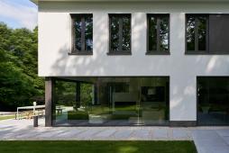 Přechod mezi zahradou a domem tvoří betonové desky a rýnský štěrkopísek. Tmavé rámové profily prosklených ploch kontrastují se světlými povrchy.