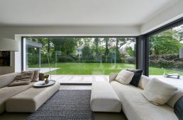 Neotvíravá prosklená stěna o ploše bezmála 13 m² téměř dokonale odstraňuje vizuální hranici mezi obytným prostorem a zahradou (Schüco AWS 75.SI)