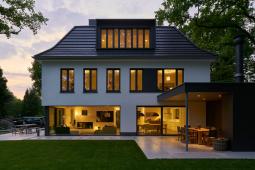 Směrem do zahrady ohraničují obytný prostor prosklené plochy na výšku místnosti, díky kterým je možné si plně vychutnat všechna roční období