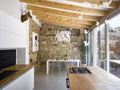 Interiéry přístavby – z jedné strany je vymezují parkány, z druhé dělicí zeď se sousedy. Kamenné zdi autoři mohli ponechat i proto, že místnost je v podstatě průchozí, tedy provětrávaná.