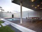 1_Hmota pavilonu tvoří jednolitý betonový odlitek. Pod jeho zadní střechou je vsazen dřevěný box, který odstupuje od vnějšího líce stavby a tvoří samostatný vložený objekt v betonové skořápce.