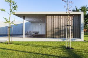 Obklad fasády ze svislých dřevěných latí řazených v mezerách mezi sebou. Vytváří jednoduchou texturu, která vložený box opticky zjemňuje.