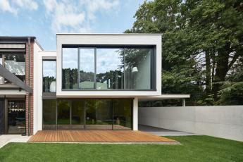 Fasáda orientovaná do zahrady. Velkoformátové prosklené plochy s úzkými profily, které jsou harmonicky rámovány omítnutými částmi objektu. Horní patro je z dřevěných trámů.
