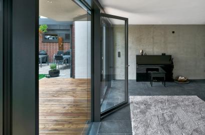 Fasáda tvořená prosklenými panely na výšku celé místnosti, které zahrnují i velkoformátové otvíravé části, umožňuje splynutí interiéru s venkovním prostorem (Schüco AWS 35 PD.SI)