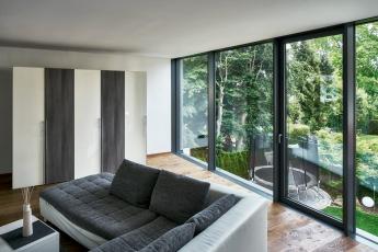 Obývací prostor v horním patře. Prosklené elementy na výšku místnosti, z nichž jeden lze otevírat, umožňují maximální přísun světla a výhled do zahrady (Schüco FWS 35 PD.SI).