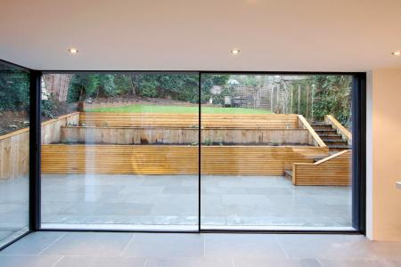 Obr. 5: Typické řešení celoskleněných odsuvných stěn, kdy posuvná část odjede do zákrytu za fixní část – polovina stěny je pak otevřená (zdroj: www.minimal-windows.com)