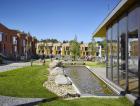 1_Mezi domy vzniklo náměstí skomponovanou zelení, sochařskou výbavou, vodní plochou alavičkami. Součástí parku je také prosklená klubovna.