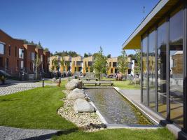 Mezi domy vzniklo náměstí skomponovanou zelení, sochařskou výbavou, vodní plochou alavičkami. Součástí parku je také prosklená klubovna.