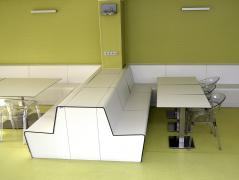 Příklad použití kompaktních desek pro nábytek a obložení stěn v interiéru. Povrch nábytku je odolný proti oděru a dostatečnou tuhost stolových desek při jejich malé tloušťce zajišťuje ocelový plech zalisovaný do vnitřních vrstev desek.