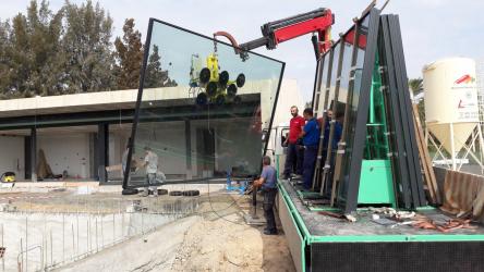 Jeřáb osazující prefabrikované panely o rozměrech 4x3 m z posuvného systému Schüco ASS 77 PD.NI
