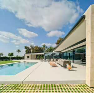 Sedlová střecha s mírným sklonem přesahuje na straně směrem k bazénu hmotu budovy, a nabízí tak další zastínění