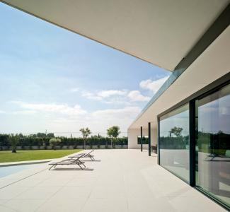 Venku i uvnitř je dlažba ze světlého přírodního kamene, která vizuálně propojuje a sjednocuje venkovní a vnitřní prostory