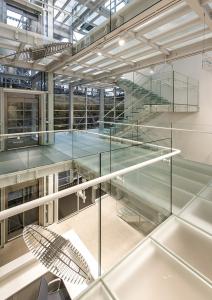 Skleněné schodiště a skleněné podlahy propouštějí sluneční paprsky celou halou a dodávají tak interiéru lehkost