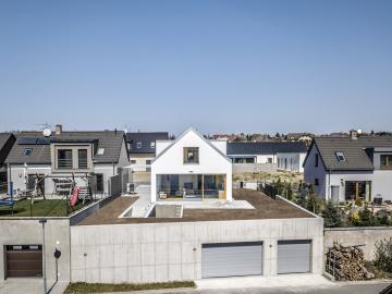 Garáž vyrovnávajíci vyškový rozdíl mezi přiléhajícími ulicemi tvoří podstavu domu